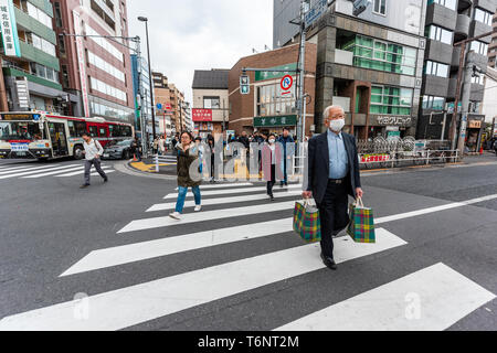 Tokyo, Japan - April 1, 2019: Shinjuku street with people in evening local man crossing road grocery shopping carrying bags after work in Kitashinjuku - Stock Photo