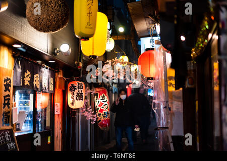 Tokyo, Japan - April 3, 2019: Memory lane alley with decorations and yellow paper lamps lanterns and people in Shinjuku area of city at night - Stock Photo