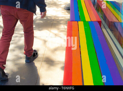 Man walking on sidewalk with wooden bench in the colors of the rainbow, symbol of gay pride - Stock Photo