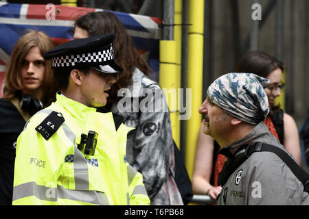 London, Greater London, UK. 1st May, 2019. Police officer is seen speaking with an Environmental activists during the protest outside the Brazilian embassy in London.Extinction Rebellion activists gathered outside Brazil embassy in London to celebrate the Amazon Rainforest's biodiversity and demand to stop the rainforest exploitation and to protect it. Credit: Andres Pantoja/SOPA Images/ZUMA Wire/Alamy Live News - Stock Photo