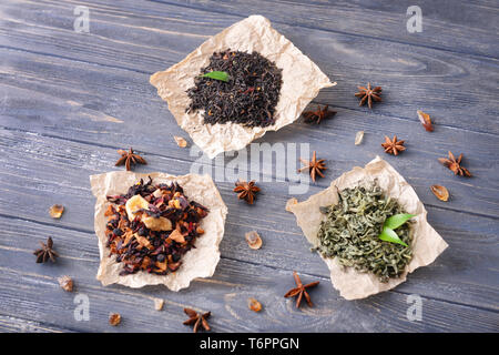 Different types of dry tea leaves on wooden background - Stock Photo