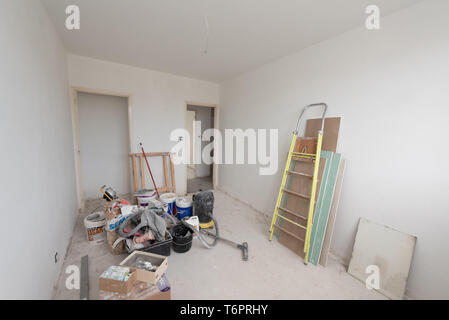 Apartment undergoing renovation: paint, floor, empty flat before refurbishment. Craftsman's tools in a room - Stock Photo