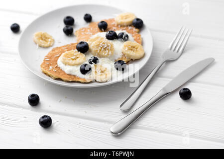Sweet oatmeal pancakes with cream, blueberry and banana. Healthy Breakfast concept. Organic food on rustic wooden table - Stock Photo