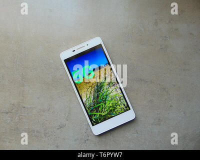 Mobile phone on gray surface at home with 5 g screen display. - Stock Photo