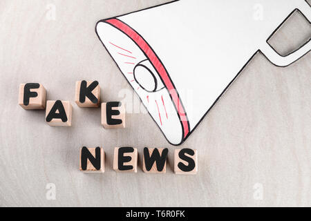 Phrase FAKE NEWS made from cubes with letters and paper megaphone on light background - Stock Photo