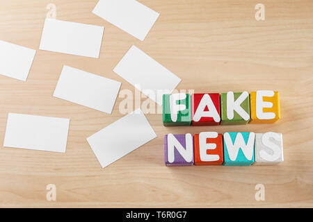 Phrase FAKE NEWS made from cubes with letters on wooden background - Stock Photo