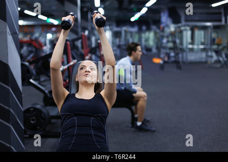 Young woman doing exercises with dumbbells in gym - Stock Photo