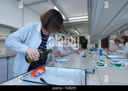 At a school chemistry lab. Female teacher conducting lesson of chemistry   for pupils wearing lab coats. Kiev, Ukraine. November 28, 2018 - Stock Photo