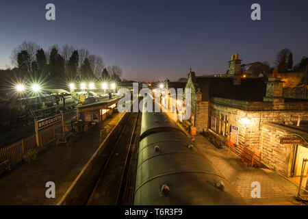 High angle, landscape view of Bridgnorth vintage railway station lit up on a cold, dark evening. Spotlights show steam & diesel locomotives in sidings. - Stock Photo