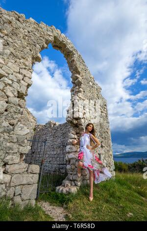 Abandoned derelict stone building house in nature natural environment teen girl is striking a pose posing hand on hip wearing long fanciful dress - Stock Photo