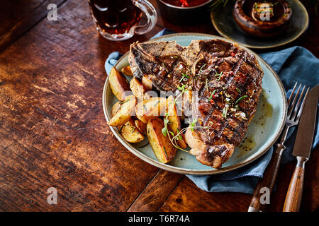 Grilled spicy T-bone steak with potato wedges served on an old rustic wooden table with copy space viewed high angle - Stock Photo