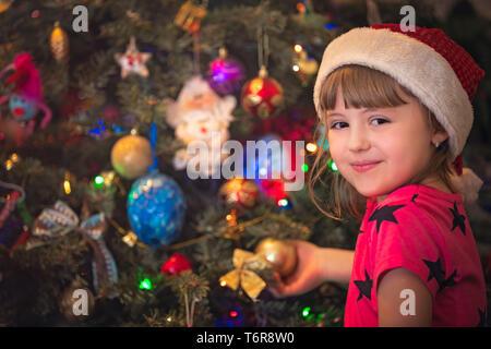 Cute happy girl decorating Christmas tree - Stock Photo