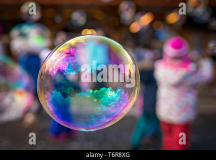 Children trying to catch giant soap bubbles - Stock Photo
