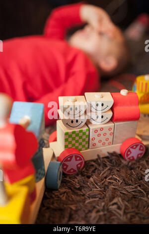 Tired boy and his toy train - Stock Photo