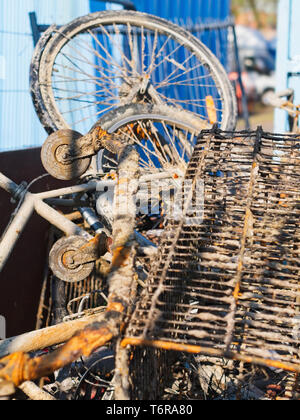 Rusty metal junk objects bicycle, shopping cart collected from the sea at an industrial quay / cargo port area. - Stock Photo