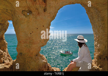 Woman looking from natural cave window to green ocean and  passing touristic boat on a sunny day - Stock Photo