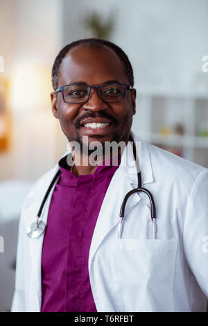 Handsome dark-skinned doctor smiling after good day at work - Stock Photo