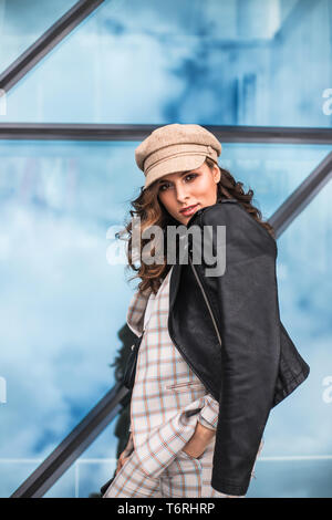 Fashionable young woman posing against glass windows outdoors. - Stock Photo
