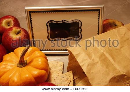 Miniature pumpkin and crispbread lies in front of a framed blank chalkboard sign - Stock Photo