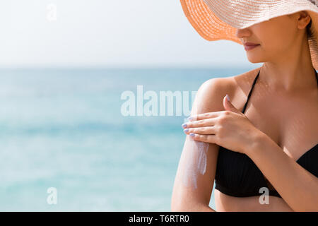 Sunscreen sunblock. Woman in a hat putting solar cream on shoulder outdoors under sunshine on beautiful summer day. - Stock Photo