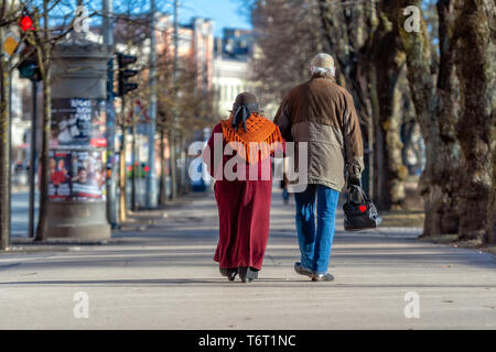 A couple of eldery people in hands are walking through the city street. Rear view. - Stock Photo