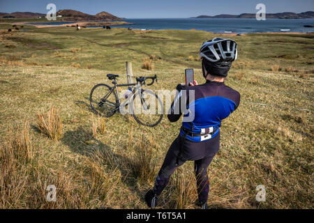 Female cyclist captures the beauty of the landscape along Loch Ewe, Poolewe, west coast of Scotland, UK. - Stock Photo
