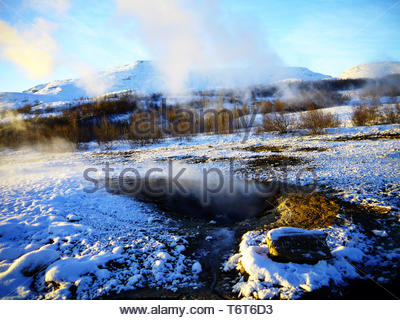 Little Geysir - close up view of Litli Geysir, Haukadalur valley, Southern Iceland, steaming with surrounding meadow covered in snow - Stock Photo