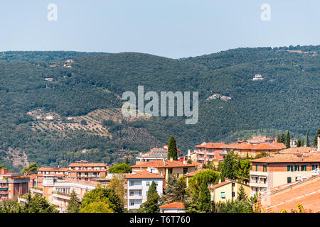 Perugia Umbria, Italy cityscape with roof of town village orange colors in sunny summer day high angle aerial view by mountains - Stock Photo