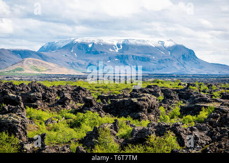 Landscape view of Iceland mountain crater in Krafla near lake Myvatn during cloudy day and many rocks - Stock Photo