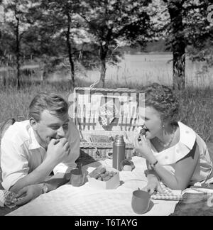 Picnic in the 1950s. A young couple are enjoying a sunny day. They have packed their food and drinks in the practical picnic case. They are eating fresh strawberries. Sweden 1956 - Stock Photo