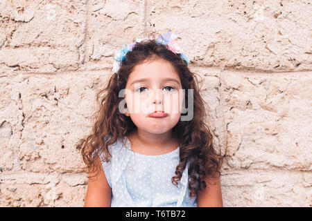 little girl making teasing with sad face, is in front of a stone wall and wears a blue dress and a flower headband - Stock Photo
