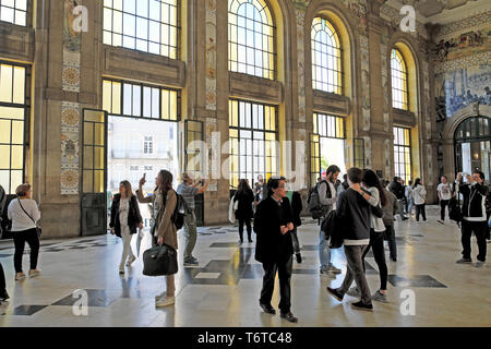 People looking at blue azulejo tiles in the Central Hall of Sao Bento railway station train station in the city of Porto Portugal Europe KATHY DEWITT - Stock Photo