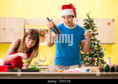 Young couple celebrating Christmas in kitchen - Stock Photo