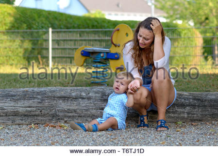 Troubled stressed young mother with her baby son - Stock Photo