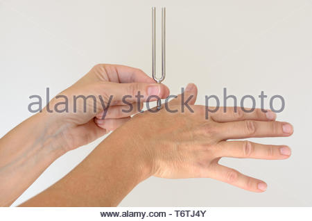 Person holding metal tuning fork against hand - Stock Photo