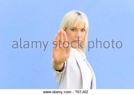 Stern young woman making a stop gesture - Stock Photo
