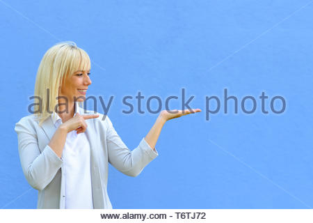 Pretty smiling woman pointing to her empty hand - Stock Photo