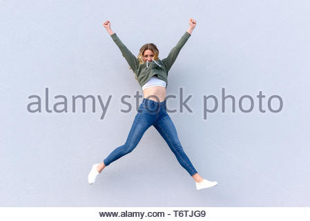 Young cheerful woman in jeans jumping into air - Stock Photo