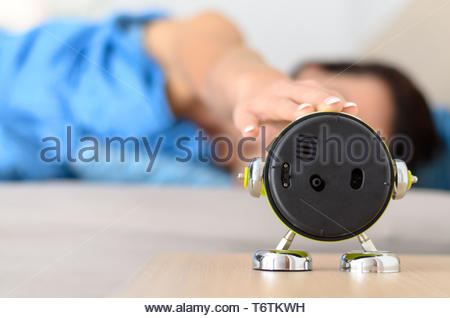 Woman stretching out to shut down the alarm - Stock Photo