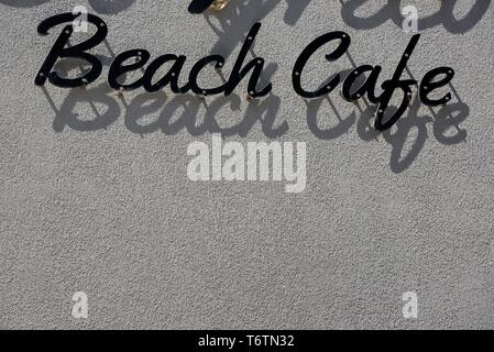 Beach cafe sign casting shadows on grey wall. - Stock Photo
