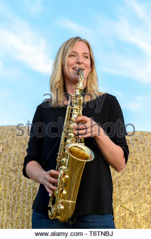 Happy young woman playing a tenor saxophone - Stock Photo