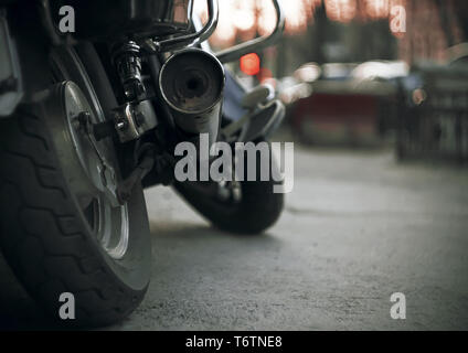 Part of a brand-new motorcycle with wheels and a dirty exhaust pipe. The motorcycle stands on the asphalt road in the dark evening and against the bac - Stock Photo