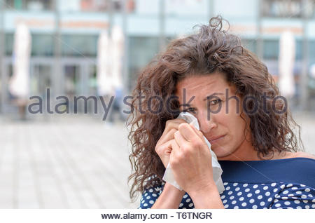 Tearful young woman wiping her eyes - Stock Photo