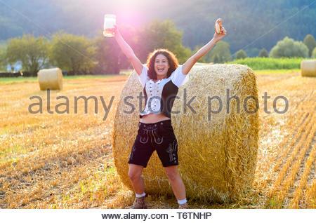 Young Bavarian woman celebrating Oktoberfest - Stock Photo