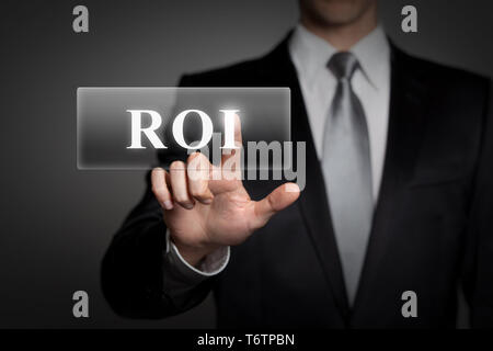 business, technology, internet, network concept - businessman in suit presses virtual touchscreen button - english word ROI (Return On Investment) - Stock Photo