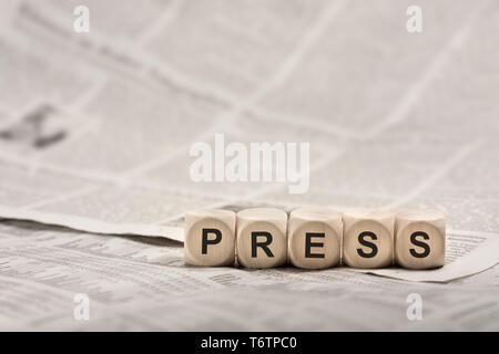 wooden cubes on newspaper forming word PRESS - Stock Photo