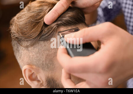 Professional barber working with client in hairdressing salon - Stock Photo