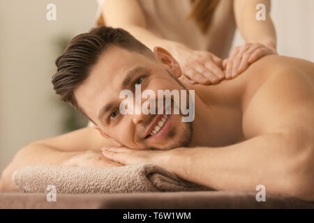 Young man receiving massage at spa salon - Stock Photo