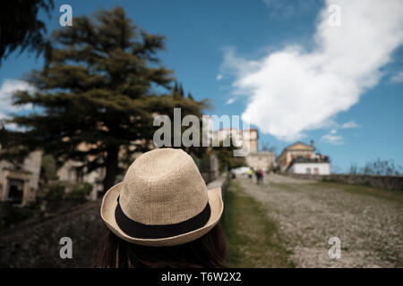 Traveler girl with Vintage Straw hat looking monumets and one of the XIVchapel along the path of the historic pilgrimage route from Sacred Mount or Sa - Stock Photo