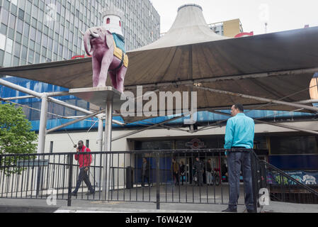 Men on the highwalk beneath the symbolic Elephant with its back-mounted castle at Elephant & Castle in Southwark, south London, on 29th April 2019, in London, England. - Stock Photo